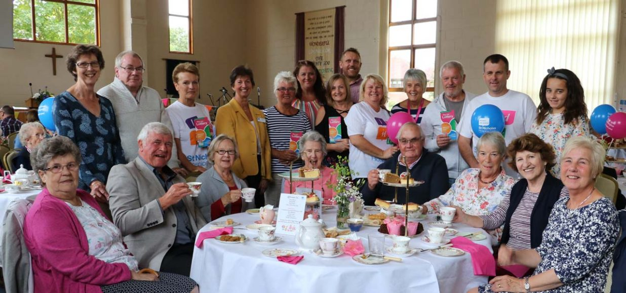 Guests raise their teacups to help mark Lottery's birthday
