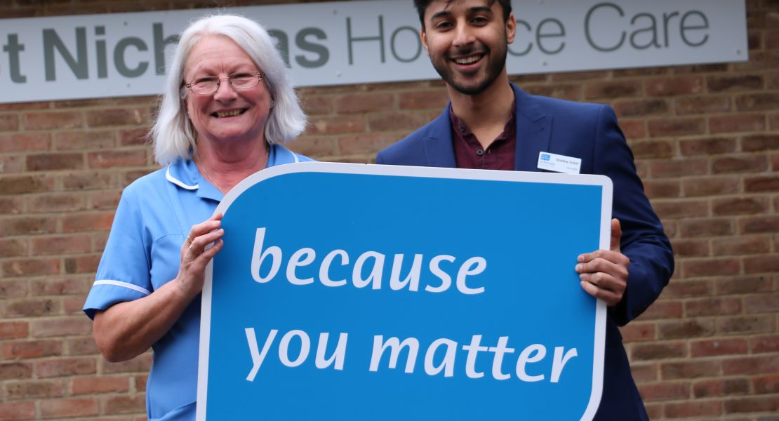 Two members of St Nic's staff holding up the Because You Matter sign