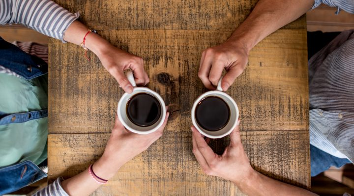 Two people facing each other drinking coffee