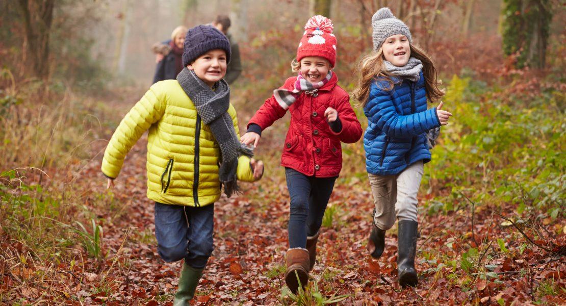 Three children running happily through a forest