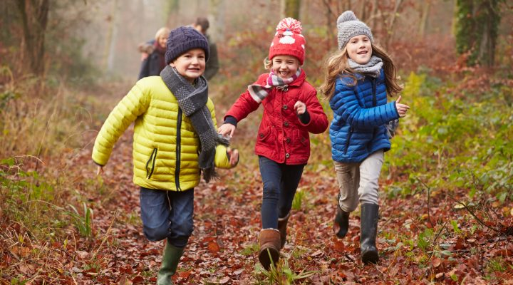 Three children running happily through a forest