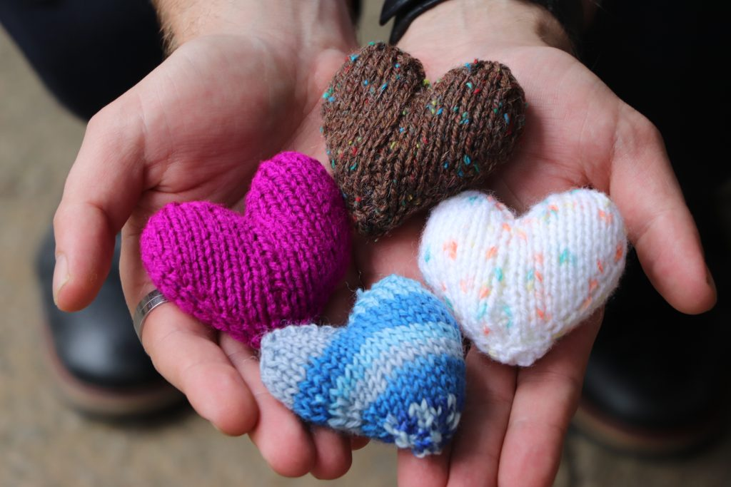 Knitted hearts presented in hands