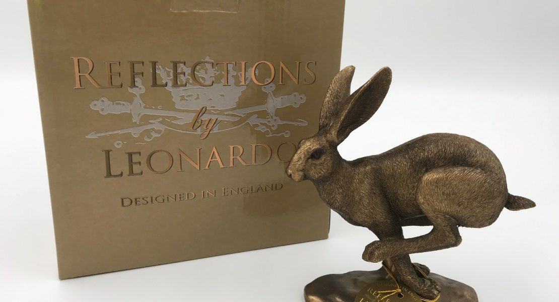 bronze ornament of a running hare on a stand with its box
